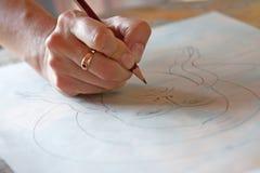 A mão com um lápis tira uma cara fotografia de stock