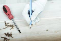 A mão com um lápis tira uma marcação para torcer o parafuso com uma chave de fenda Imagem de Stock