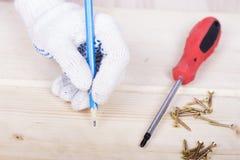 A mão com um lápis tira uma marcação para torcer o parafuso com uma chave de fenda Imagens de Stock Royalty Free