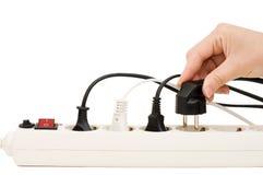 Mão com um plugue elétrico e um soquete imagem de stock