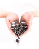 Mão com um punhado das moedas isoladas no fundo branco Imagem de Stock