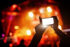 A mão com um smartphone grava o festival de música ao vivo, concerto vivo, mostra na fase imagens de stock