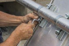 A mão com uma chave aperta a porca Fotos de Stock Royalty Free