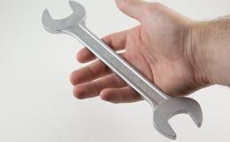Mão com uma chave de chave inglesa em um fundo branco Imagem de Stock Royalty Free