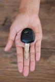 Mão com uma chave do carro no fundo de madeira Imagem de Stock Royalty Free