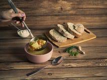 Mão com uma concha derrama a sopa de ervilha Alimento rústico fotografia de stock royalty free