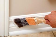 Mão com uma escova de pintura Fotos de Stock
