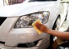 Mão com uma limpeza do microfiber o lustro do carro imagem de stock