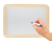 Mão com uma pena no whiteboard de madeira Fotografia de Stock Royalty Free