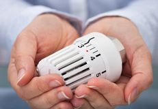 Mão com a válvula do sistema de aquecimento imagem de stock