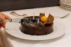 A mão corta o bolo de chocolate para o aniversário fotos de stock royalty free