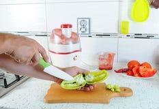 A mão cortou com uma faca a pimenta verde em uma placa de corte Legumes frescos de Juicing Suco fresco imagens de stock royalty free