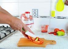 A mão cortou com uma faca a pimenta vermelha em uma placa de corte Legumes frescos de Juicing Suco fresco fotos de stock royalty free