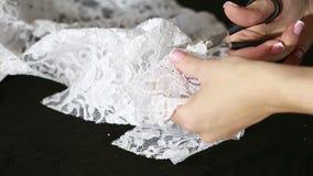 A mão cortou a tela branca com as tesouras da costureira que cortam um pano vídeos de arquivo