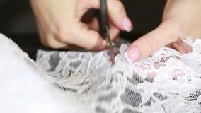 A mão cortou a tela branca com as tesouras da costureira que cortam um pano filme