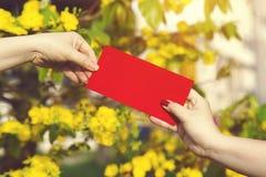 A mão dá o dinheiro nos envelopes vermelhos - prisioneiro de guerra do ANG ou pacote vermelho a algum Fotos de Stock