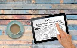 Mão da caça de emprego on-line com os anúncios do emprego da leitura da tabuleta do computador na tabela com café Imagens de Stock