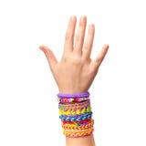 Mão da criança com os braceletes de borracha coloridos do tear do arco-íris isolados Imagens de Stock