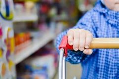 Mão da criança pequena que aferra-se ao carrinho de compras, azul Imagem de Stock