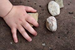 Mão da criança que toca em uma pedra Fotografia de Stock Royalty Free