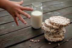 A mão da criança toma em casa o leite pão estaladiço saboroso na tabela de madeira do fundo Fotografia de Stock Royalty Free