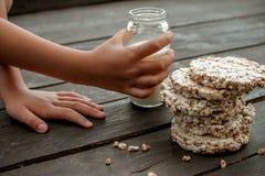A mão da criança toma em casa o leite pão estaladiço saboroso na tabela de madeira do fundo Foto de Stock