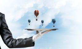 Mão da empregada de mesa que apresenta balões na bandeja Fotografia de Stock Royalty Free