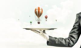 Mão da empregada de mesa que apresenta balões na bandeja Foto de Stock Royalty Free