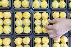 A mão da fêmea decora da pastelaria dos choux com creme fotografia de stock royalty free