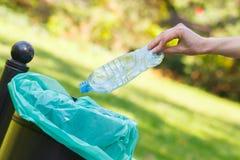 Mão da garrafa de jogo da mulher no escaninho de reciclagem, desordem de ambiental foto de stock royalty free