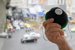 Mão da máscara protetora da terra arrendada do homem superior para a proteção da poluição atmosférica da poluição na cidade fotos de stock royalty free