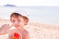 Mão da mãe caucasiano que aplica o suncream a ela Fotografia de Stock
