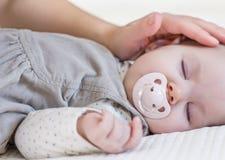 Mão da mãe que acaricia seu sono do bebê Imagens de Stock