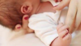 A mão da mãe toca nos dedos pequenos na cama branca, close up vídeos de arquivo