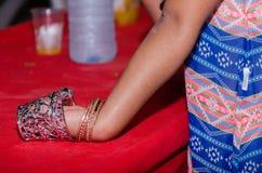 A mão da menina com os braceletes no copo Imagem de Stock Royalty Free