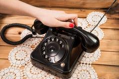 Mão da menina que guarda auriculares velhos do telefone em toalhas de mesa do laço e no fundo de madeira foto de stock royalty free