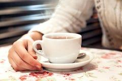 A mão da menina que guarda um copo do chá Imagens de Stock