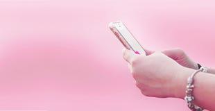 Mão da menina que guarda um smartphone em um fundo cor-de-rosa fotos de stock