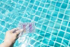 Mão da menina que mergulha o jogo do teste dos testes de água na água clara da piscina para testar o pH e o cloro imagens de stock royalty free