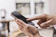 Mão da menina que toca no telefone esperto móvel do ecrã táctil Imagem de Stock