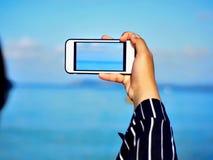 Mão da menina que toma a foto na praia foto de stock royalty free