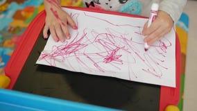 A mão da menina tira um marcador no papel filme