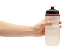 Mão da moça que guarda a garrafa de água do esporte foto de stock