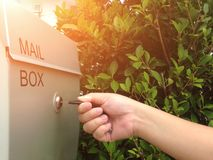 A mão da mulher abre a caixa postal com a chave na frente da casa fotografia de stock