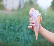 A mão da mulher bonita que guarda um cone de gelado colorido Fim acima outdoor Adultos novos imagem de stock royalty free