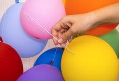Mão da mulher com a agulha de confecção de malhas pronta para estalar um balão amarelo foto de stock royalty free