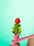 Mão da mulher com alimento do vegetariano e as fitas de medição Foto de Stock Royalty Free