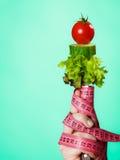 Mão da mulher com alimento do vegetariano e as fitas de medição Foto de Stock