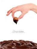 Mão da mulher com bombom do chocolate imagem de stock royalty free