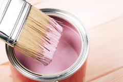 A mão da mulher com a escova branca que aplica a pintura cor-de-rosa na mobília de madeira fotografia de stock royalty free